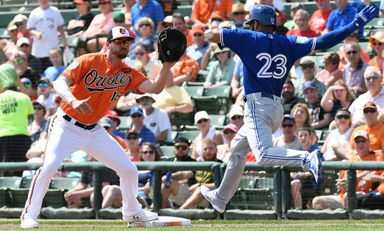 Mar 13, 2019; Sarasota, FL, USA; Baltimore Orioles infielder Trey Mancini (16) waits for the ball as Toronto Blue Jays outfielder Dalton Pompey (23) attempts to reach first base in the first inning of the spring training game at Ed Smith Stadium. Mandatory Credit: Jonathan Dyer-USA TODAY Sports