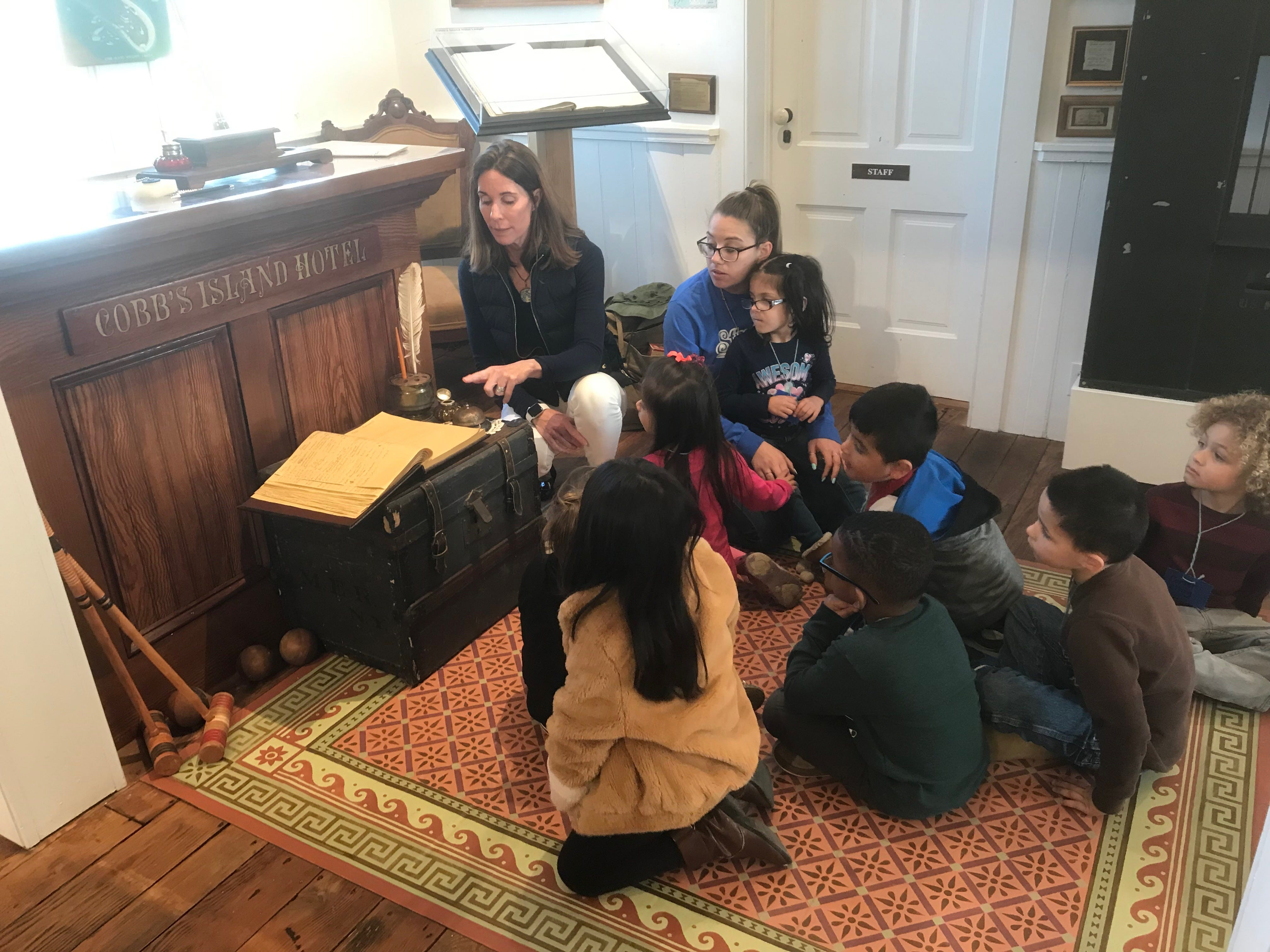 Sally Dickinson, education director, demonstrates how guests at the Cobb's Island Hotel checked in during a My First Field Trip event with Occohannock Elementary School pre-kindergarten students on Tuesday, March 26, 2019  at the Barrier Islands Center in Machipongo, Virginia.