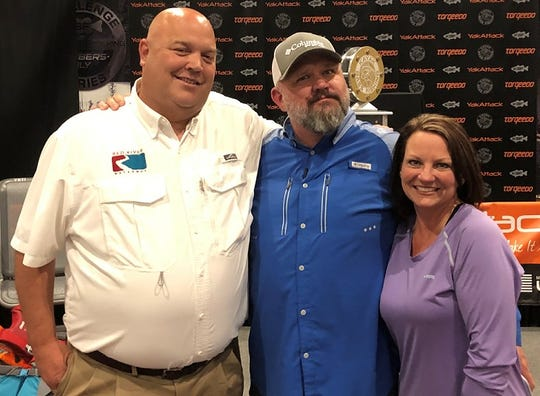 Kayak Bass Fishing owner Chad Hoover (left) and his wife, Kristi, pose with Red River Waterway representative Eric Gilmore