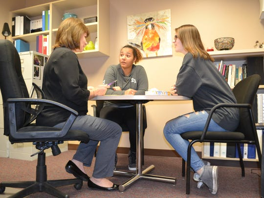 Washington High School counselor Patti Lake-Torbert talks with sophomores Angelique Kiyombo and Norilyn Binney about the stress of the upcoming standardized testing season Tuesday, March 26, 2019. She's one of nearly 20 traditional high school counselors handling a case load that's almost double the national standard.