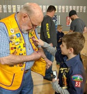 The Dells Lions club is the charter sponsor of the Boy Scouts Pinewood Derby each year. At the March 23 event, seven-year old Tayden Hagen won the trophy for Best in Class and was intrigued by the badges and pins on Lion Tom Earley's vest.