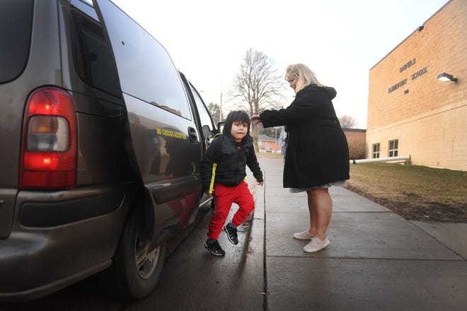 Garfield Elementary School Principal Kristin Skogstad greets kindergartener Wanbli Roberts, 5, as he gets out of a taxi at school Wednesday, March 27, at the school in Sioux Falls. Garfield Elementary is one of the SFSD campuses with the highest student mobility rates and higher number of economically disadvantaged students. To give those students a better sense of educational consistency, the school has partnered with churches to pay for transportation costs to keep those students on their home campuses. That includes taxi rides to and from home.