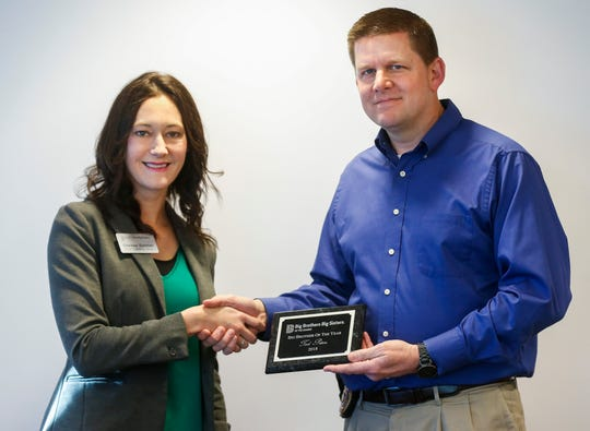 Chelsea Dykman, chief operating officer of Big Brothers Big Sisters of the Ozarks, presents Captain Tad Peters, of the Springfield Police Department, with the Big Brother of the Year award on Wednesday, March 27, 2019.