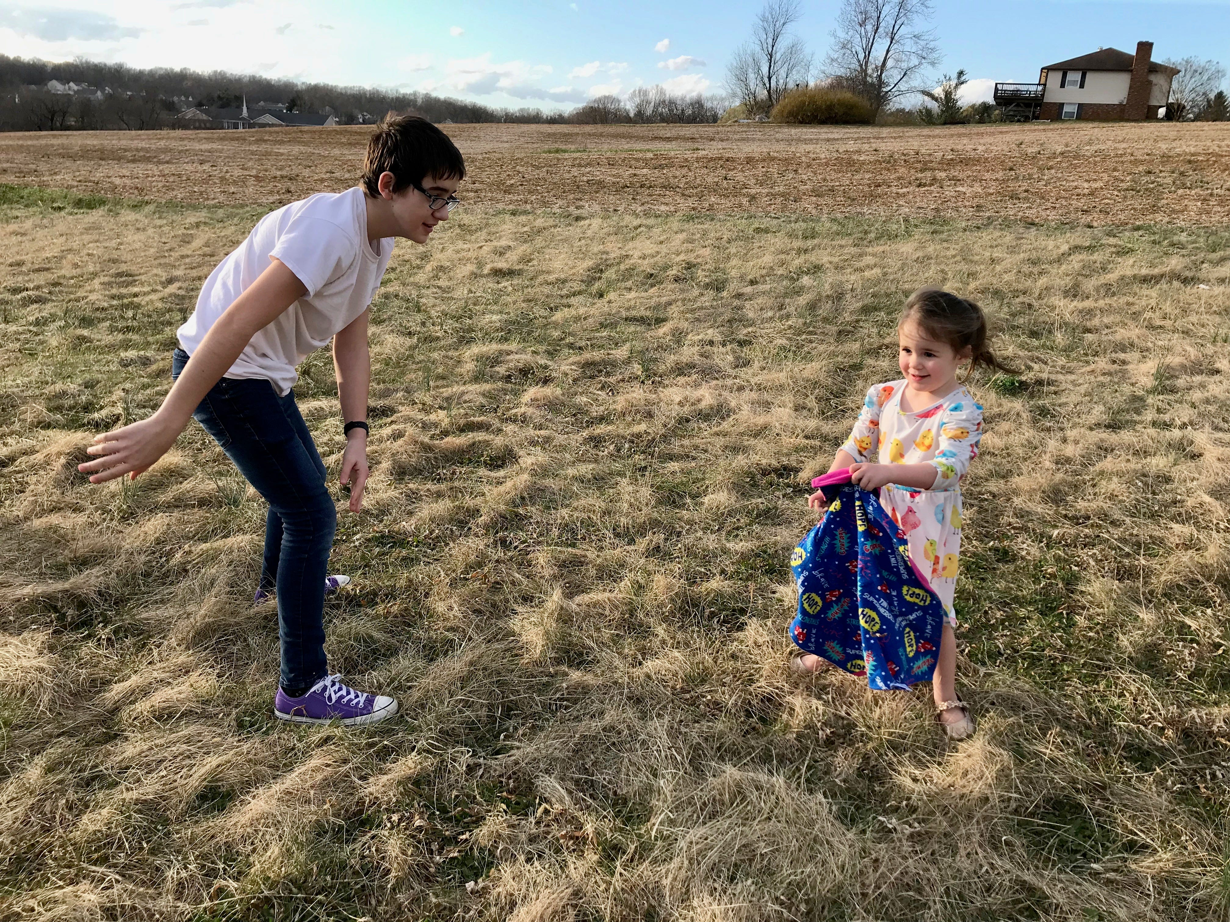 Wyatt Bussey, 14, plays with his sister Rebecca Bussey, 3, in their backyard of their home in Ladd, Virginia, on Friday, March 15, 2019. Rebecca has the rare disease Systemic Juvenile Idiopathic Arthritis. She is holding her Tiny Superheroes cape made by an organization to give hope to kids with chronic diseases.