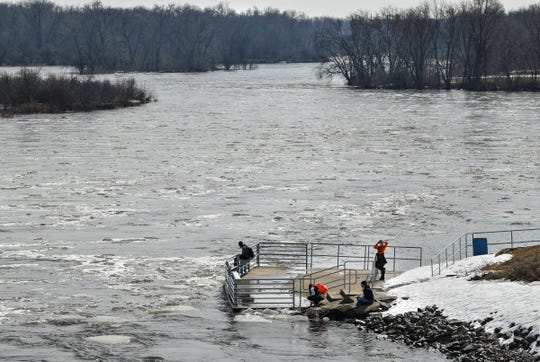 People watch the rapidly flowing water underneath the St. Cloud Dam on the Mississippi River Wednesday, March 27, near St. Cloud State University.