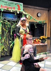 "The carnivorous Audrey II (Leslie Gray) hovers above the botanical genius, Seymour Krelborn (Nate Jones) and Audrey (Leah Bakan) in the Young Actors Theatre production of ""Little Shop of Horrors"""
