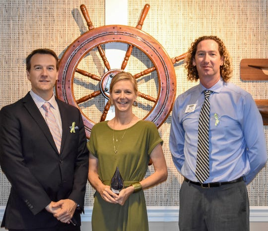 Missy Weiss, center, received the Environmental Champion Award from Keep Indian River Beautiful board members Douglass Bailor, left, and Chris Woodruff.