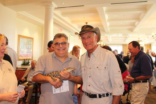 America's favorite zookeeper Jack Hanna, right, talks with Ed Abraira, a Busch Wildlife Sanctuary volunteer wildlife rescuer holding a juvenile Florida alligator, at Jupiter Hills Country Club.