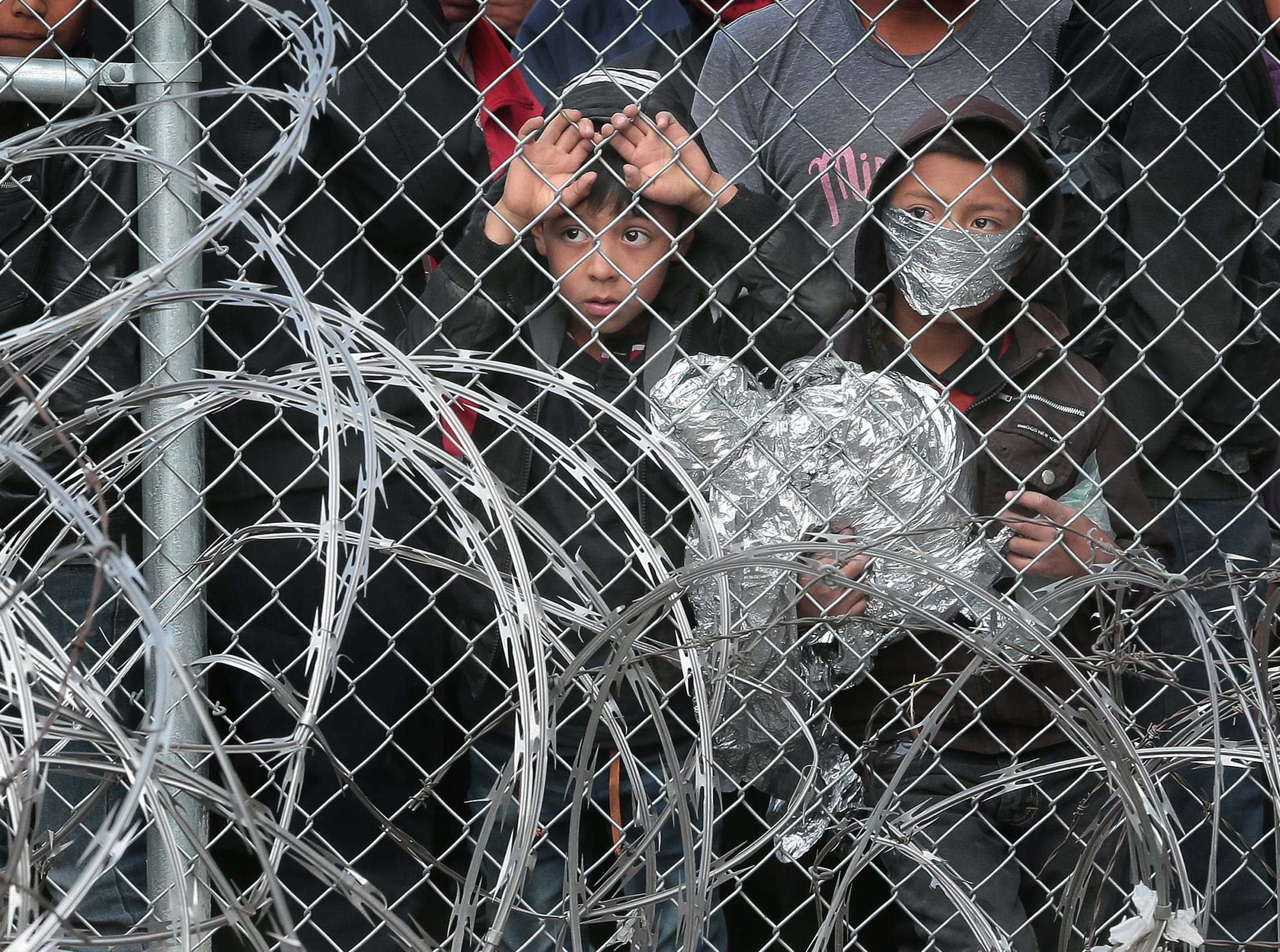 Hundreds of migrants are being held beneath the Paso Del Norte International Bridge in El Paso as U.S. Customs and Border Protection has run out of space to process the asylum seekers. Above, two boys look out from the fence at the bridge as protestors demand their release.