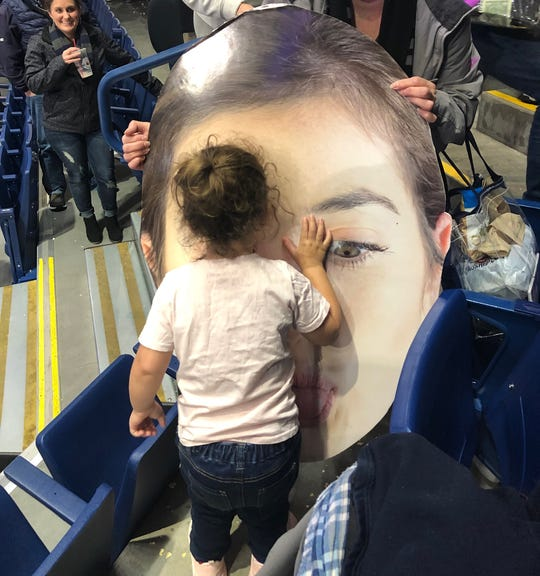 "Katie Campbell's daughter Ava kisses a ""big head"" poster of her mother's face after a recent Gonzaga University women's basketball game."