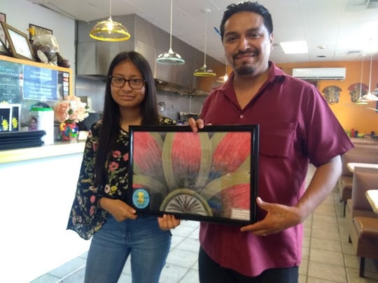Giselle Merino, who was an eighth grader in the ExCEL program in Bridgeton, and Luis Angel Berdejo of Los Molcajetes, a restaurant on Irving Avenue in Bridgeton, admire Merino's artwork. The artwork will be displayed in the restaurant as part of Bridgeton Public Library's Gold Brush Awards Program.
