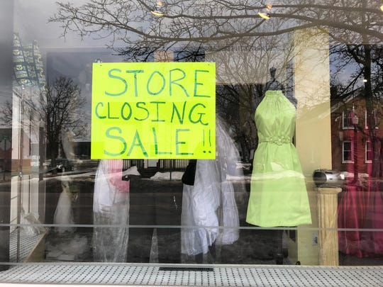 A sidewalk window at With This Ring on Third Street displays dresses for sale.