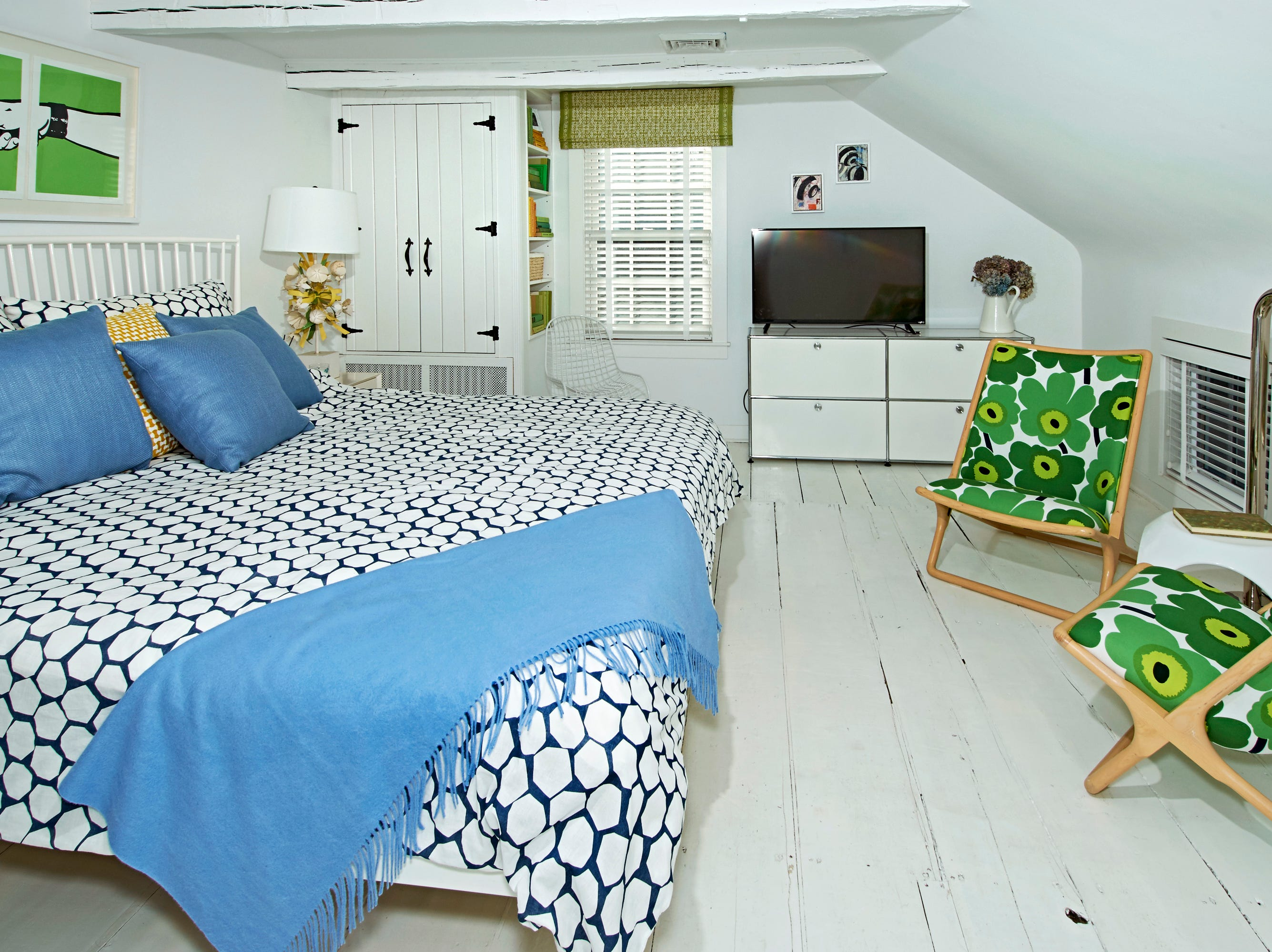 One of the bedrooms. The use of bright colors throughout the all-white home gives it a fresh and fun perspective.