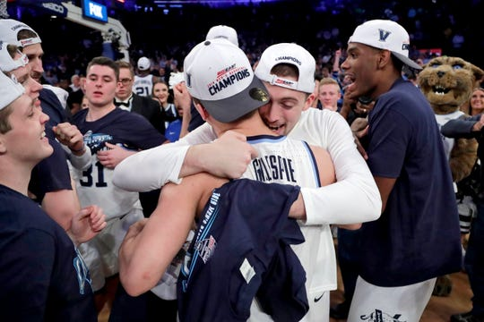 Villanova guard Joe Cremo, center, hugs guard Collin Gillespie, left, after defeating Seton Hall 74-72 in an NCAA college basketball game in the championship of the Big East Conference tournament, Saturday, March 16, 2019, in New York.