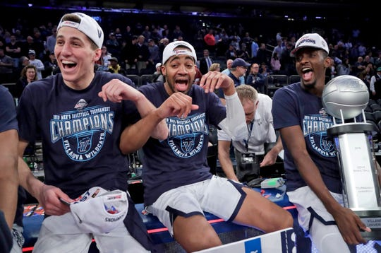 Villanova's Collin Gillespie, left, Phil Booth, and Dhamir Cosby-Roundtree celebrate after defeating Seton Hall 74-72 in an NCAA college basketball game in the championship of the Big East Conference tournament, Saturday, March 16, 2019, in New York.