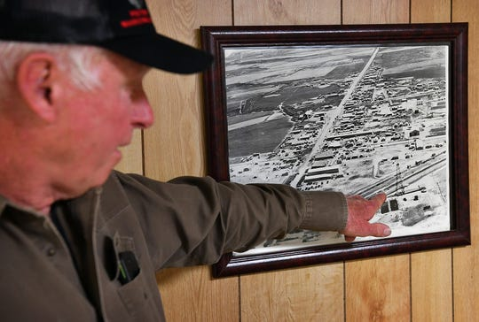 Johnny Ray Crenshaw points out the Fleming #2 oil well derrick in an aerial photo of Kamay, Texas taken in 1938. The well is still in production today. Oil was discovered in the area in 1919, making Kamay a boomtown one year after Burkburnett.
