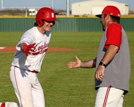 Holliday's Logan Whitling celebrates with head coach Brad Blassingame after hitting a homerun against Bowie Tuesday, March 26, 2019, in Holliday.