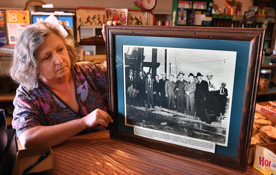 Kathy Whyrick, owner of Kathy's Korner, shows a historic photo with businessmen on the site of the Jack Kadane No.1 Charles Mangold well. The gusher brought 2,000 barrels a day and a new oil boom to the area.
