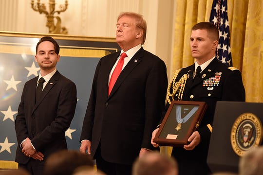 President Trump stands next to Trevor Oliver during the citation for the Congressional Medal of Honor presentation to Travis W. Atkins