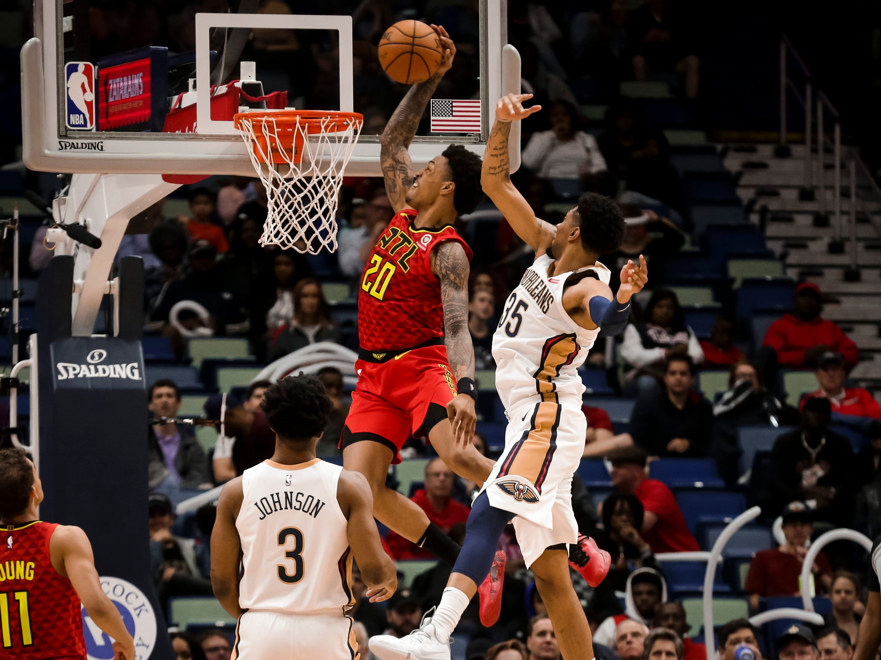 March 26: Atlanta Hawks forward John Collins (20) dunks over New Orleans Pelicans forward Christian Wood (35) during the second half at the Smoothie King Center.