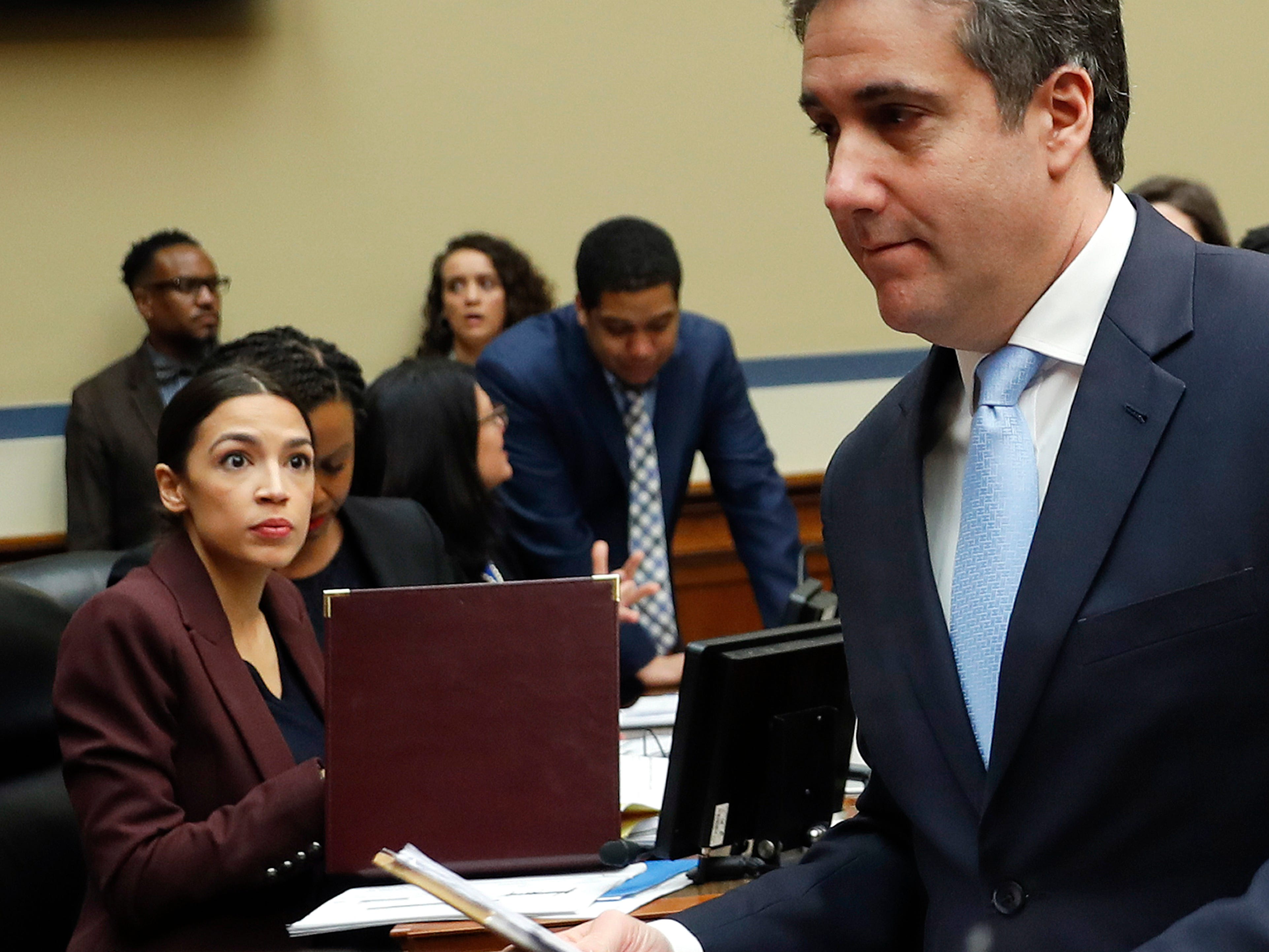 Michael Cohen, right, President Donald Trump's former lawyer, walks past committee member Rep. Alexandria Ocasio-Cortez, D-N.Y., center, during a break in Cohen's testimony before the House Oversight and Reform Committee on Capitol Hill in Washington, Wednesday, Feb. 27, 2019. (AP Photo/Pablo Martinez Monsivais) ORG XMIT: DCPM104