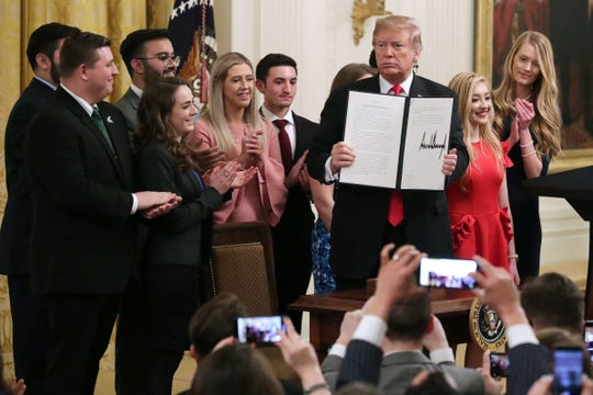 President Donald Trump holds up an executive order he signed to protect free speech on college campuses on March 21, 2019 at the White House.