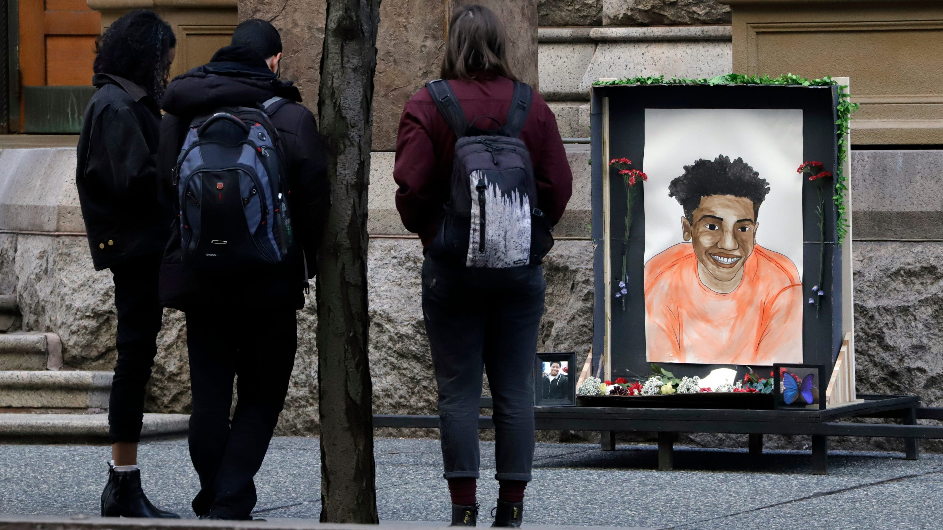 People gather around a memorial drawing of Antwon Rose II who was fatally shot as he fled during a traffic stop.