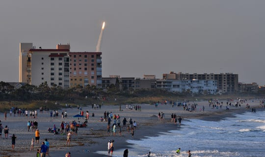 Crowds on the beach in Cocoa Beach and Cape Canaveral watch the launch of the United Launch Alliance Atlas V rocket from from Launch Complex 41 at Cape Canaveral Air Force Station Saturday night at 7:13  p.m. The rocket launched a multi-payload mission known as Air Force Space Command-11, or AFSPC-11. (Via OlyDrop)
