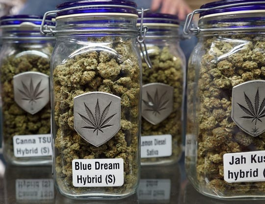 Jar of dried marijuana flowers sits inside a screen cabinet at the Denver-based Medicine Man marijuana store. This marijuana is legal to sell to adults under Colorado law, but remains illegal at federal level.