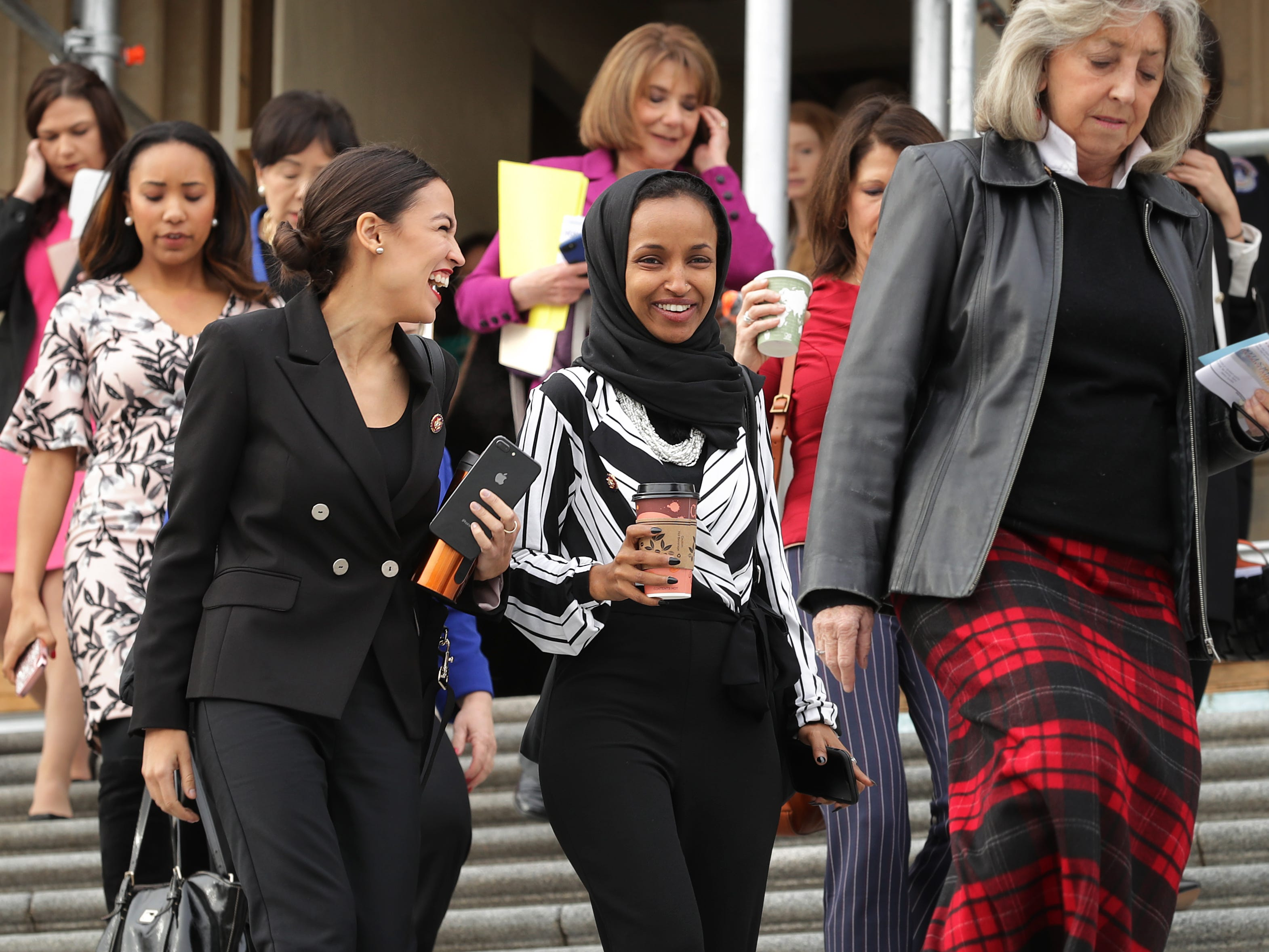 WASHINGTON, DC - JANUARY 04: Rep. Alexandria Ocasio-Cortez (D-NY) (L) and Rep. Ilhan Omar (D-MN) (C) join their fellow House Democratic women for a portrait in front of the U.S. Capitol January 04, 2019 in Washington, DC. The 116th Congress has the biggest number of female members ever while the number of Democratic women in the House has grown from 16 to 89 since 1989. (Photo by Chip Somodevilla/Getty Images) ***BESTPIX*** ORG XMIT: 775277340 ORIG FILE ID: 1089771236