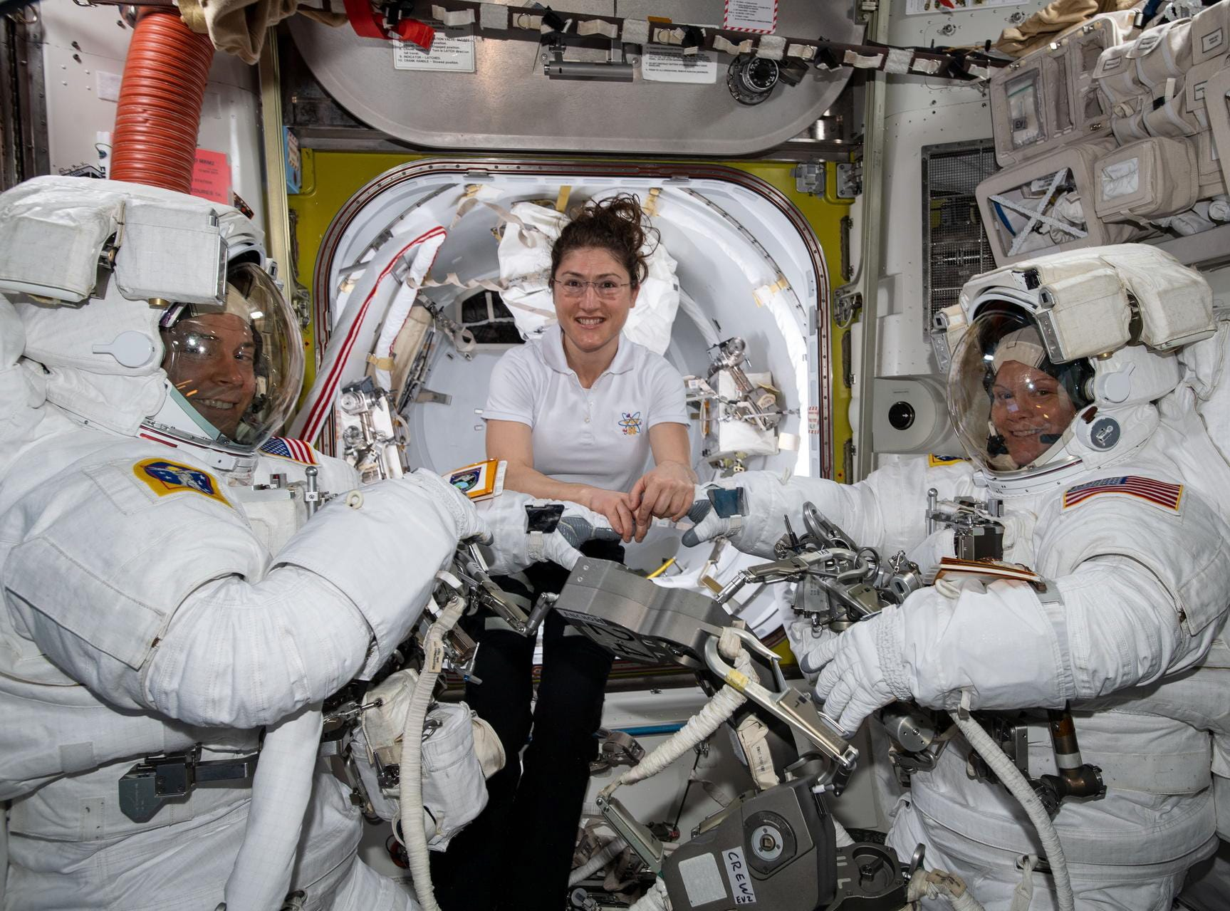 NASA astronaut Christina Koch assists fellow astronauts Nick Hague and Anne McClain  in their spacesuits shortly before they begin the first spacewalk of their careers, aboard the International Space Station (ISS), March, 22, 2019  NASA cancelled the first all-female spacewalk which was scheduled for March 29,  2019, citing spacesuit issues.