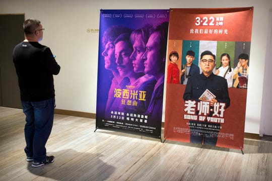 "A customer looks at a movie poster for the film ""Bohemian Rhapsody"" at a movie theater in Beijing on March 27, 2019."
