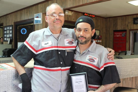 Omar Ortiz (right) holds the award he received Wednesday for saving the life of Jeff Hart (left) when Hart caught on fire while working at Auto Tech in Pineville.