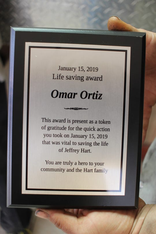 Omar Ortiz holds the plaque he received for saving the life of his coworker, Jeff Hart, after he caught on fire on Jan. 15.