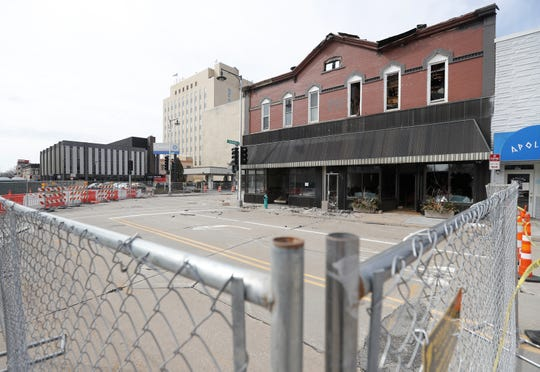 A chain-link fence still surrounds the downtown building badly damaged in a fire earlier this month. The building is expected to be torn down in the next few weeks.