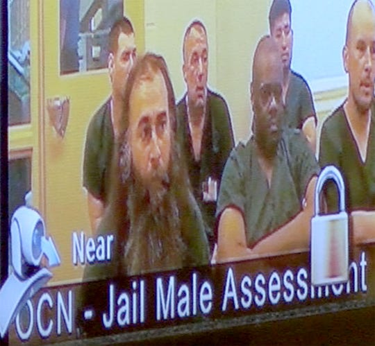 Brian Keith Combs (front left), 44, of Jackson, Ashley Combs' biological father, is shown during a video conference hearing in State Superior Court in Toms River Thursday, March 28, 2019.  He is facing felony charges of interfering with the custody of a minor and obstruction.  Ashley's biological mother Mechelle Combs, 39, is facing a charge of obstruction.