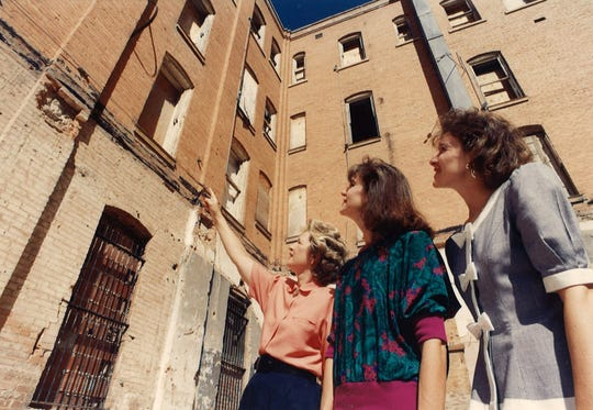 Los Aficionados members, from left, Kathy Moreland, Leigh Black and Jill Forehand study the abandoned Drake Hotel with hopes of visualizing its transformation into the Grace Cultural Center in September 1990.