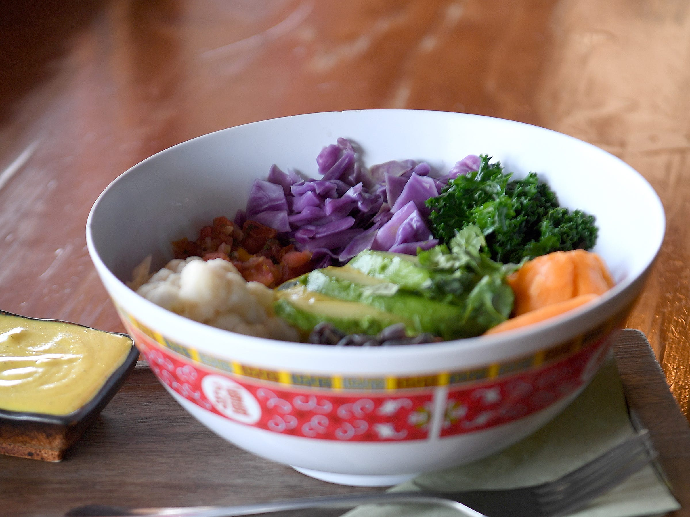 The Yum bowl at Dobra Tea's West Asheville location is jasmine rice, seasoned black beans, steamed kale, sweet potato, cauliflower, red cabbage, avocado and salsa all paired with a signature Yum sauce.