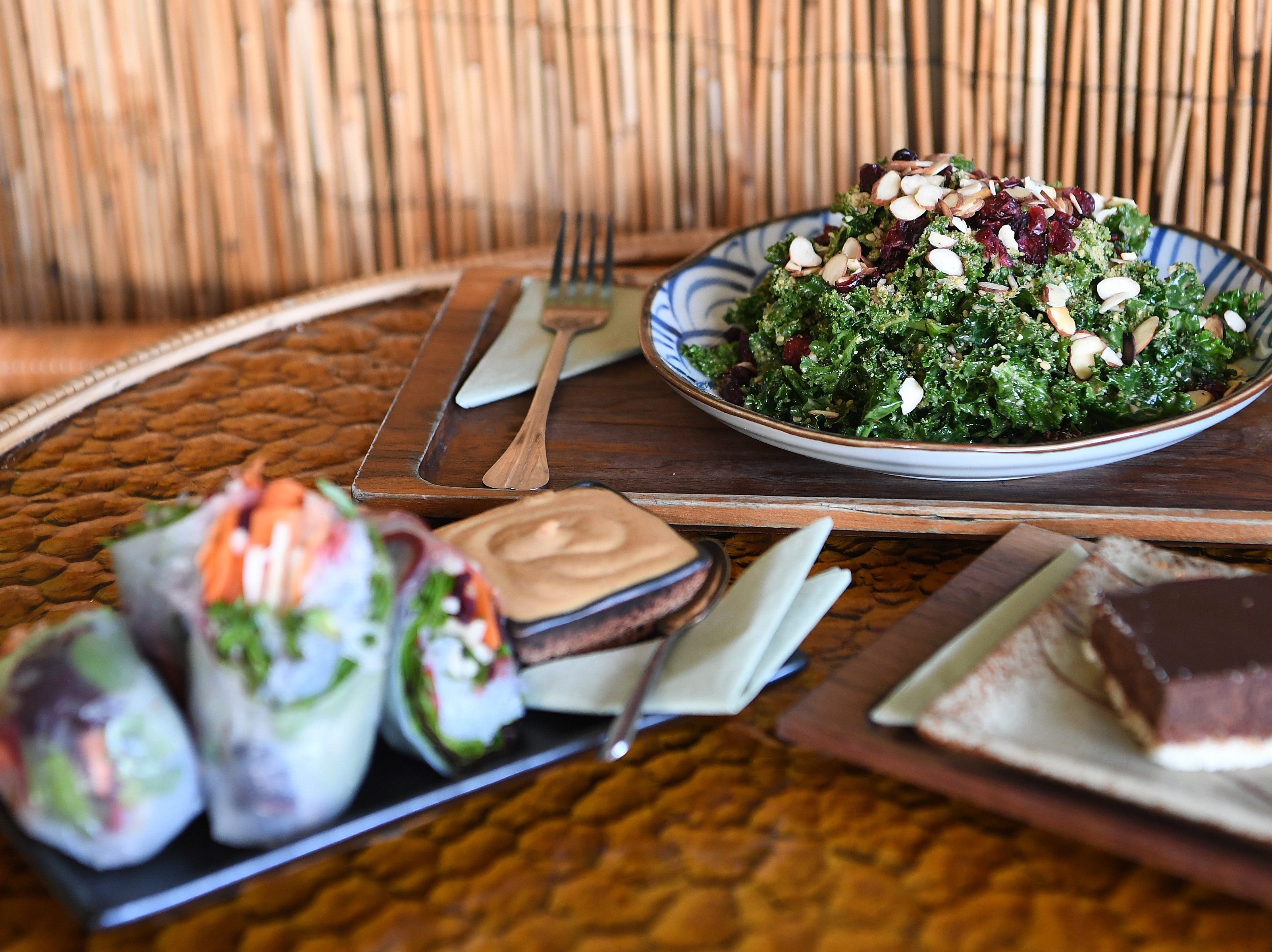 The kale caesar salad at Dobra Tea's West Asheville location is tossed in dairy-free caesar dressing and topped with dried cranberries, sliced almonds and vegan seed parmesan. Shown here with spring rolls and an almond joyful bar.