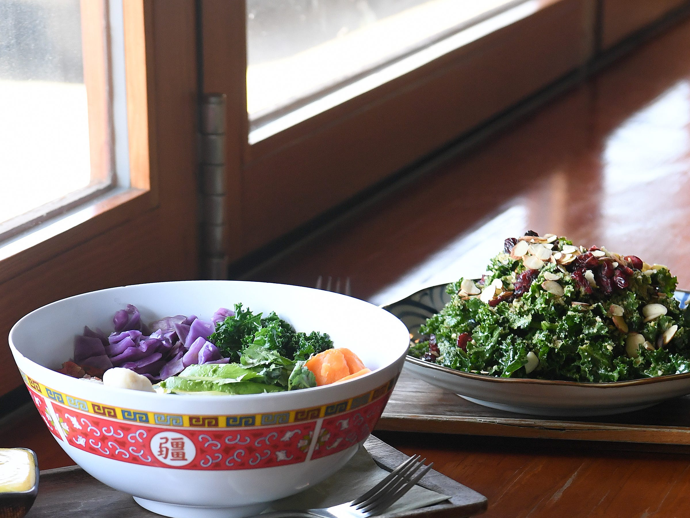 The Yum Bowl, kale caesar salad, almond joyful bar and spring rolls are all food options available at Dobra Tea's West Asheville location.
