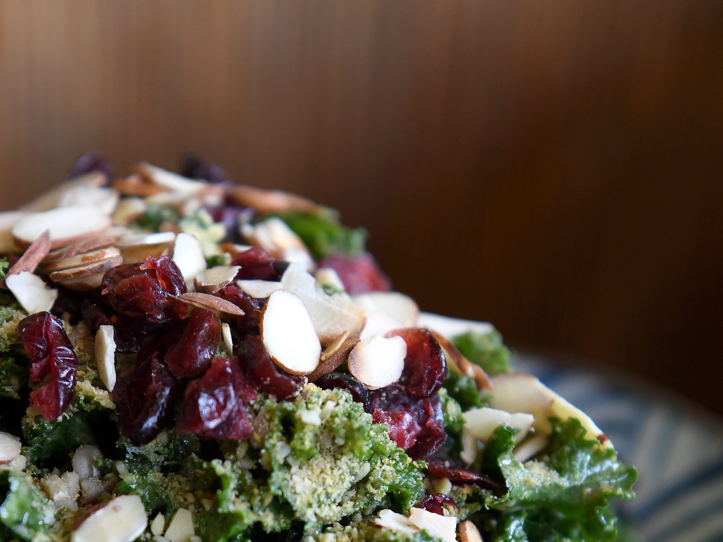 The kale caesar salad at Dobra Tea's West Asheville location is tossed in dairy-free caesar dressing and topped with dried cranberries, sliced almonds and vegan seed parmesan.