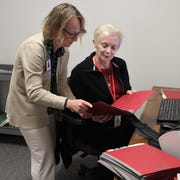 Calhoun County Probate Court Register Cindy Rude, at left, and volunteer, Maureen Vire, at right, review paper files before they are electronically scanned.