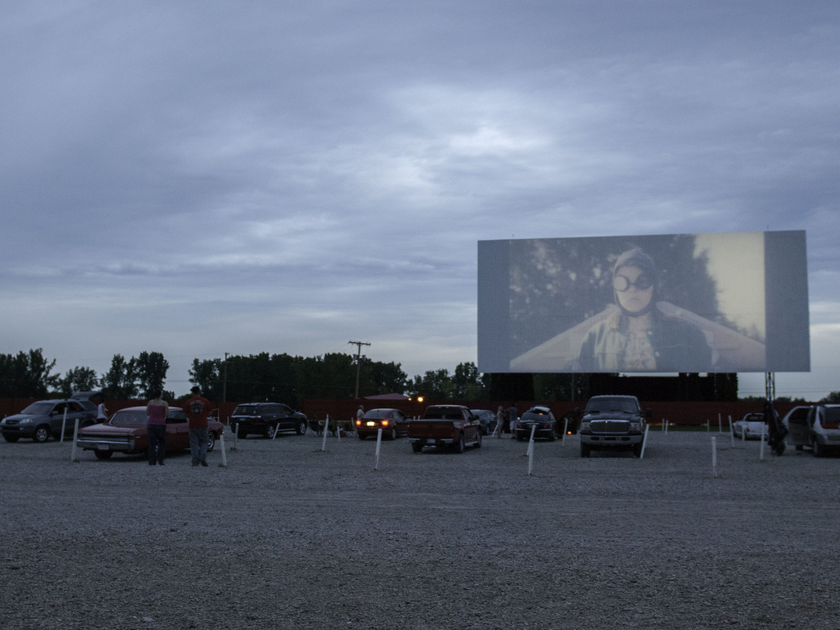 Cars gather around a screen for a double feature just before the sun sets at the Capri Drive-In in Coldwater.