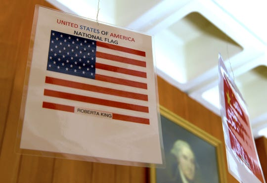 Flags bearing the names and countries of origin of the 13 victims of the 2009 mass shooting hang in the conference room of the American Civic Center in Binghamton.