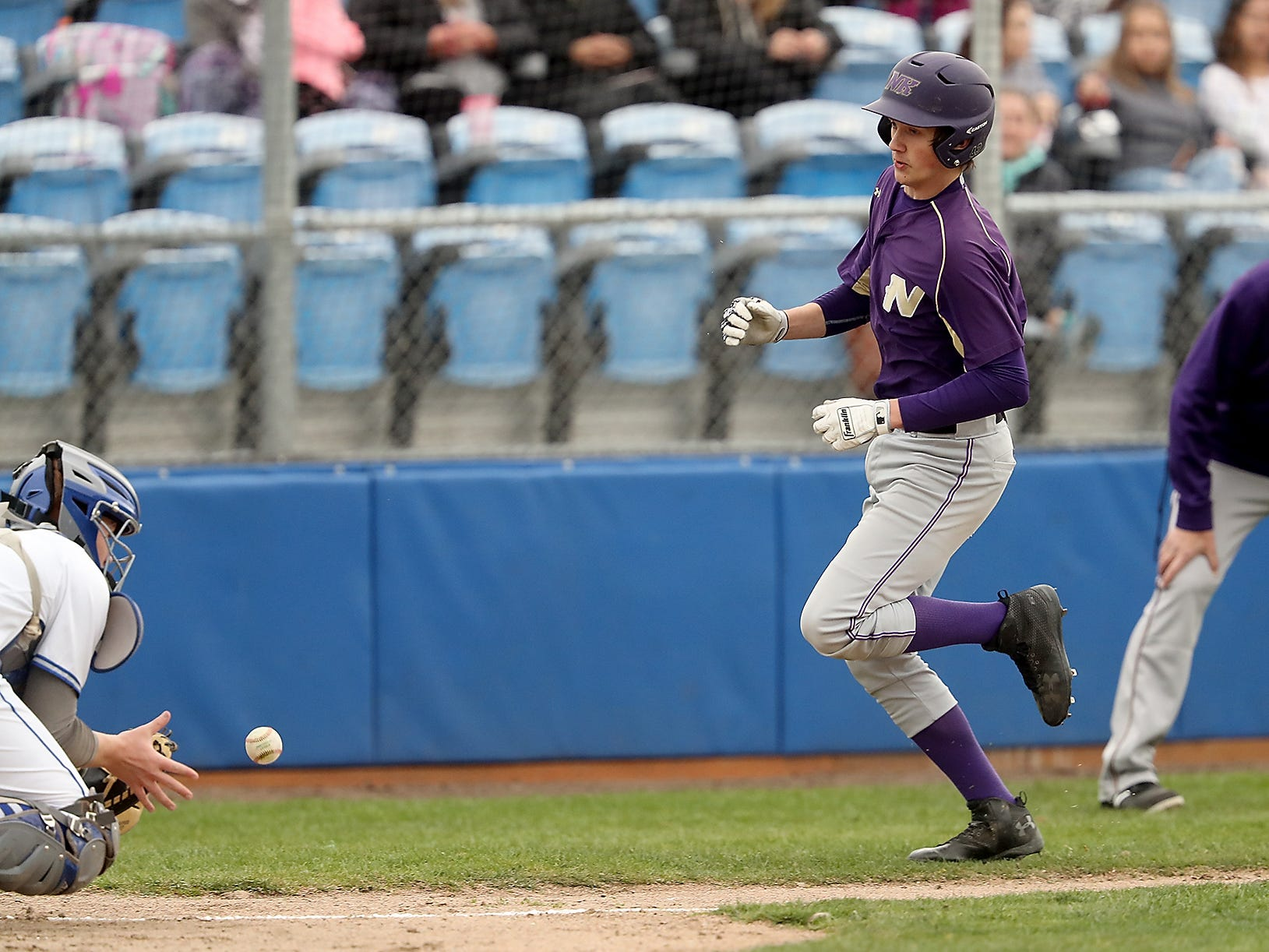 North Kitsap's Ryland Schmidt races the throw to Olympic catcher Charlie Hennessy at Gene Lobe Field on Wednesday, March 27, 2019.