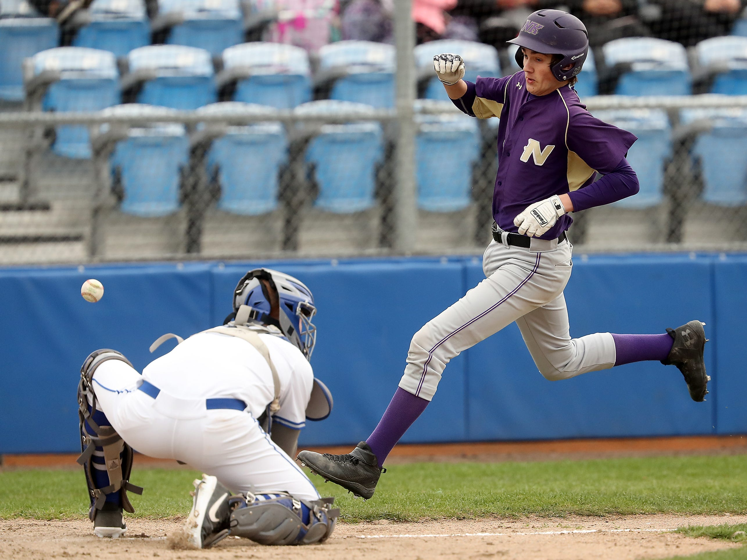Olympic catcher Charlie Hennessy misses the catch as North Kitsap's Ryland Schmidt heads for home during their game at Gene Lobe Field on Wednesday, March 27, 2019.
