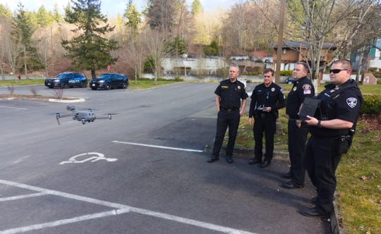 Poulsbo police and fire department officials look on during a demonstration flight of the police department's new drone.