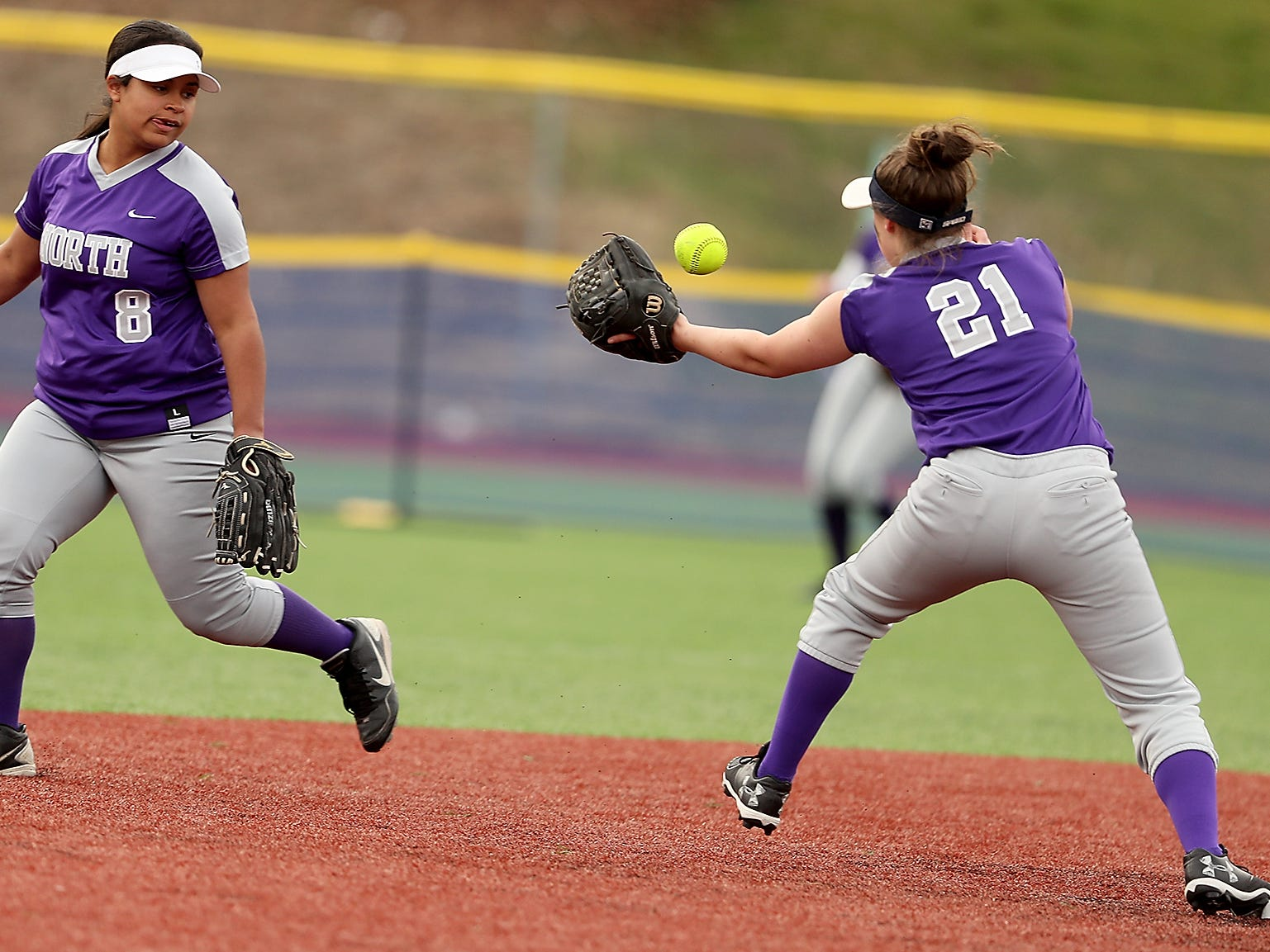 North Kitsap's Alicia Goetz (8) lobs the ball to Iyreland Lawson (21) for an out at second against Olympic at Gene Lobe Field on Wednesday, March 27, 2019.