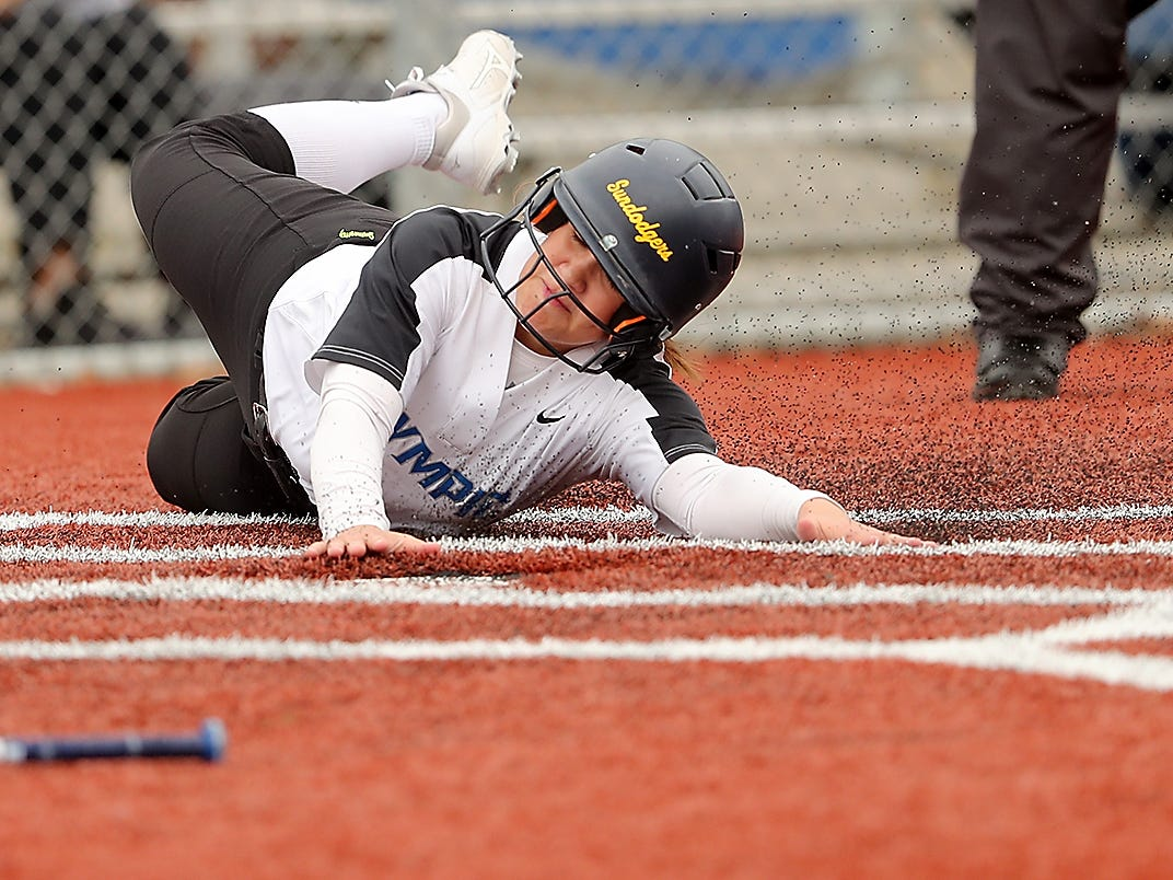 Olympic's Sadie Chipley slides safely into home against North Kitsap at Gene Lobe Field on Wednesday, March 27, 2019.