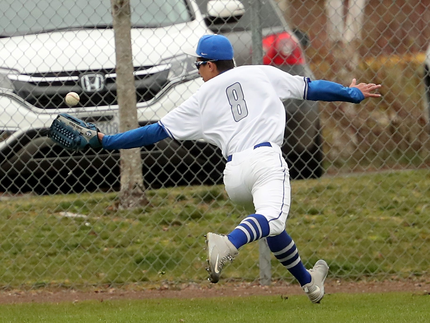 Olympic's Jaeden Orteza bobbles a catch by the fence aganst North Kitsap at Gene Lobe Field on Wednesday, March 27, 2019.